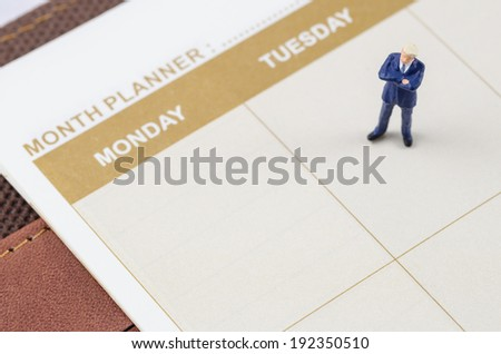 miniature businessman standing on the planner book - stock photo