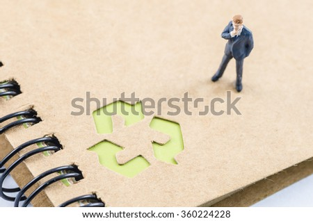 miniature businessman standing on the recycle notebook