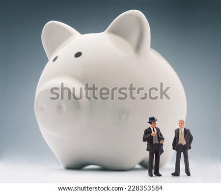 Miniature businessmen analyzing piggy bank - stock photo
