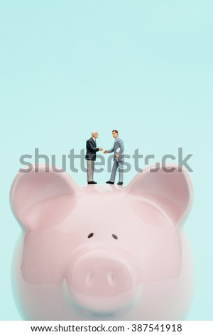 Miniature businessmen making a deal on top of a piggy bank - stock photo