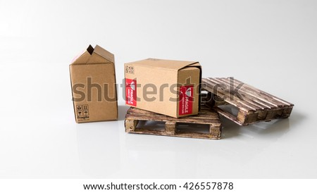 Miniature cardboard box with Fragile sticker on wooden pallet. Concept of handle with care or courier business. Isolated on white background. Slightly de-focused and close-up shot. Copy space. - stock photo