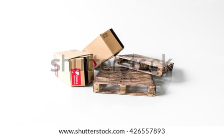 Miniature cardboard box with Fragile sticker on wooden pallet. Concept of handle with care or courier business. Isolated on white background. Slightly de-focused and close-up shot. Copy space.