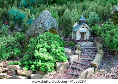 Miniature church with tiny forest in the background - stock photo