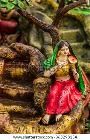 Miniature clay model of a village girl playing musical instrument beside a fountain. - stock photo