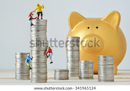 Miniature climbers team climbing on stack of coins - stock photo