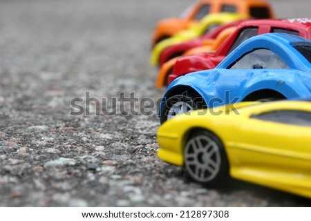 miniature colorful cars standing in line on road sale concept. Different colored cars - blue, yellow, orange, white and red color cars standing next  - car agent sale concept