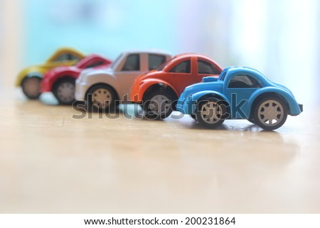 miniature colorful cars standing in line showroom sale concept. Different colored cars - blue, yellow, orange, white and red color cars standing next to each other - car agent sale concept - stock photo