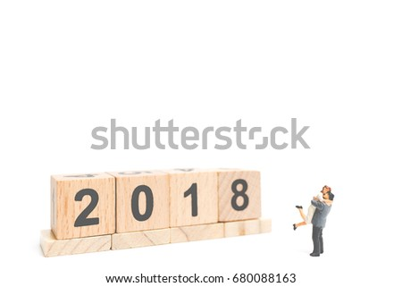 Miniature couple hugging on wooden block number 2018 with a space for text