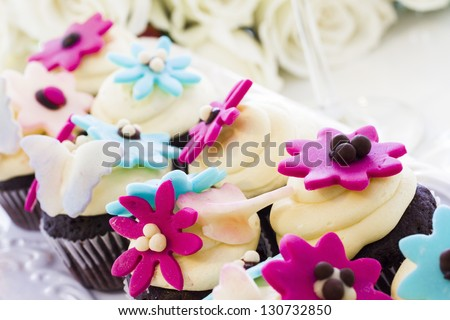 Miniature cupcakes decorated with bright flowers for the wedding party.