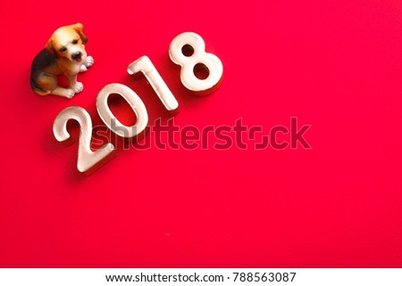 Miniature dog with year 2018 on red background.