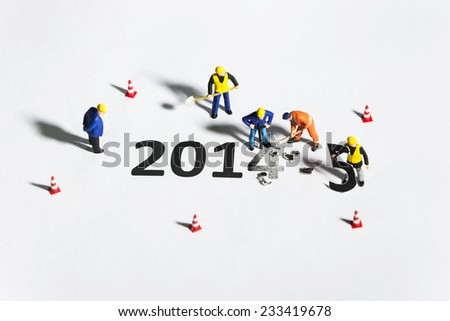 Miniature engineer or technician change represents the new year 2014- 2015 - stock photo