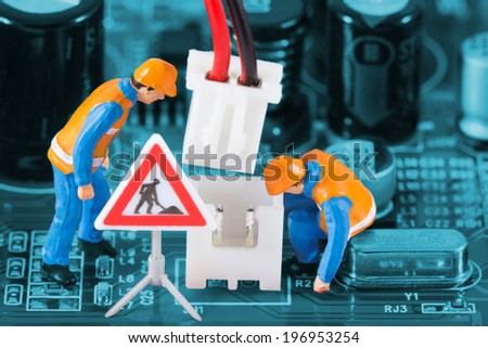 Miniature engineers fixing wire connector on circuit board. Computer repair concept. Close-up view. - stock photo