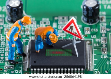 Miniature engineers looking at code on chip of circuit board. Computer repair concept. Close-up view. - stock photo