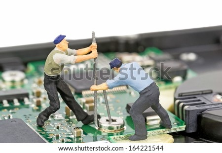 Miniature engineers repairing a computer hard drive - stock photo