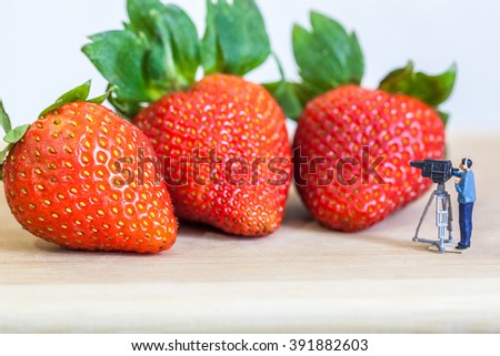 miniature figure (cinematographer) with ripe red strawberries on wooden table