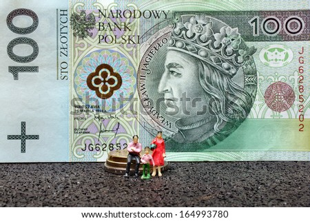 Miniature figure family on a background of polish money  - stock photo