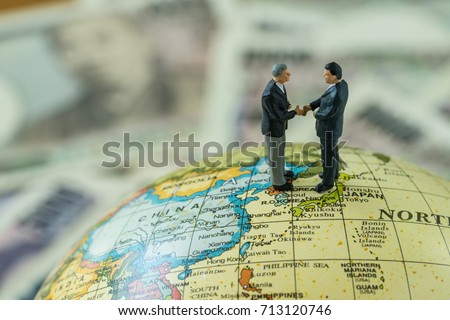 Miniature figure men handshaking standing on north korea and japan map globe as peace and war agreement negotiation concept.