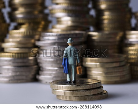 Miniature figure standing on a pile of coins - stock photo