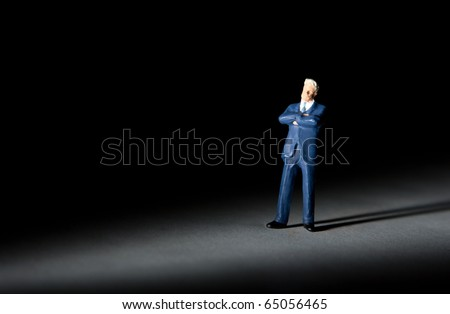 Miniature figurine of successful businessman with crossed arms - stock photo