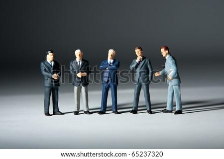 Miniature figurines of successful business team. Five statuettes - stock photo