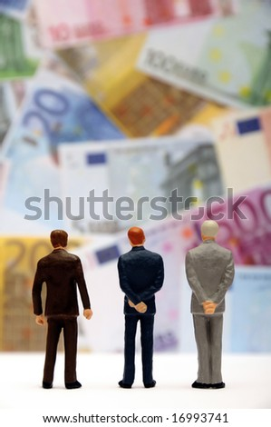 miniature figurines standing in front of a wall of euro banknotes - stock photo