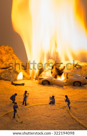Miniature firemen at a car crash scene in flames - stock photo