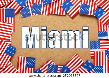 Miniature flags of the United States of America form a border on brown card around the name of the city of Miami