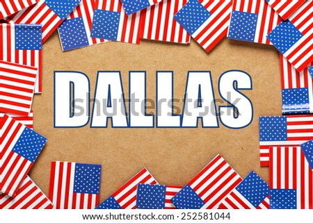 Miniature flags of the United States of America form a border on brown card around the name of the city of Dallas - stock photo