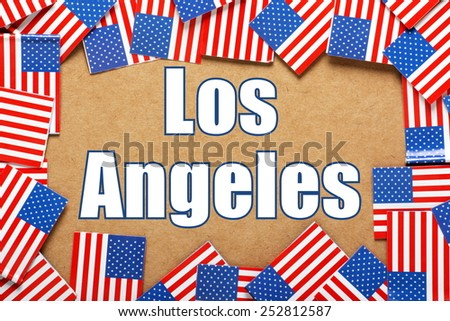 Miniature flags of the United States of America form a border on brown card around the name of the city of Los Angeles