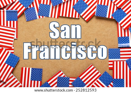 Miniature flags of the United States of America form a border on brown card around the name of the city of San Francisco