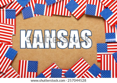 Miniature flags of the United States of America form a border on brown card around the name of the state of Kansas - stock photo