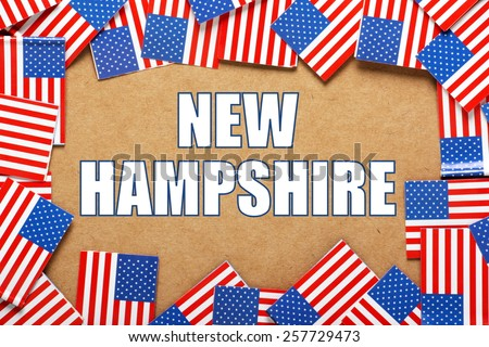 Miniature flags of the United States of America form a border on brown card around the name of the state of New Hampshire
