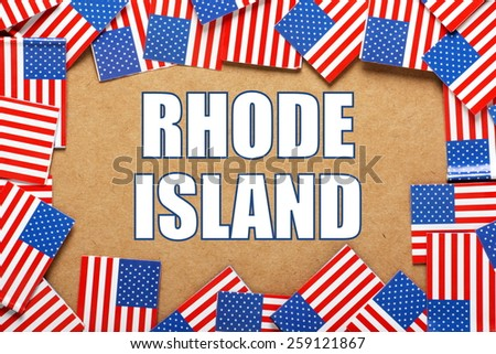Miniature flags of the United States of America form a border on brown card around the name of the state of Rhode Island