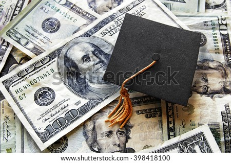 Miniature graduation cap on hundred dollar bills                                - stock photo