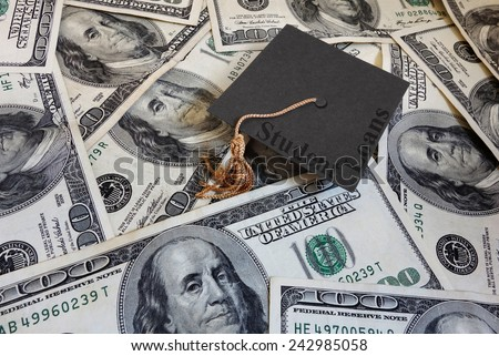 Miniature graduation cap with Student Loans text, on assorted cash                                - stock photo