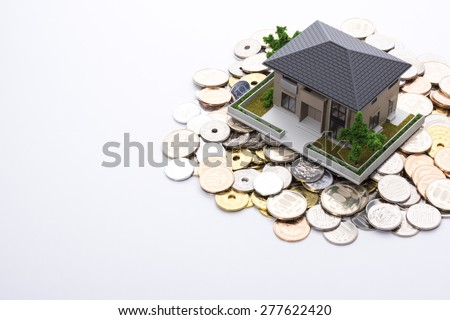 Miniature house and coins - stock photo