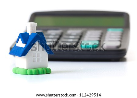 Miniature house in front of calculator concept for mortgage, home finances or saving for a house - stock photo