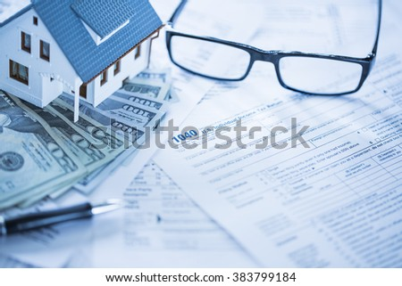Miniature house with money and tax forms. - stock photo