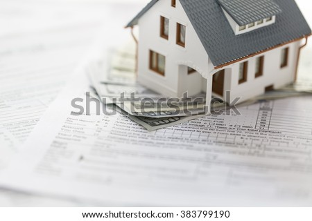 Miniature house with money and tax forms.