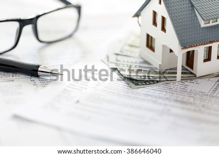 Miniature house with money on tax papers. - stock photo