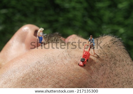 Miniature Life People Mowing Hair off a Mans Face - stock photo