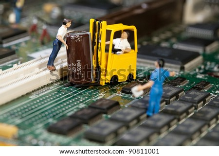 Miniature maintenance team. A team of miniture toy figurines busy with repair and maintance. - stock photo
