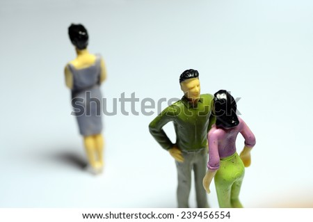 Miniature Man chatting with woman, and single woman turning back - stock photo