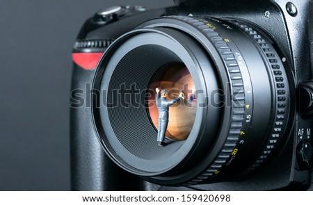 Miniature man cleaning camera lens. Macro photo - stock photo