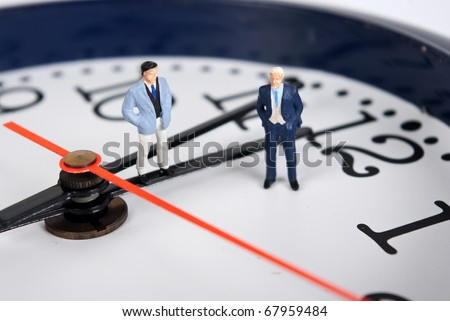 miniature man on the clock - stock photo