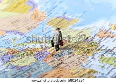 miniature man on world map - stock photo