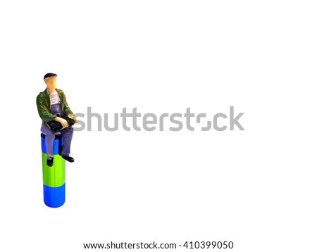 Miniature man sitting on AA battery isolated on white with room for copy space - stock photo