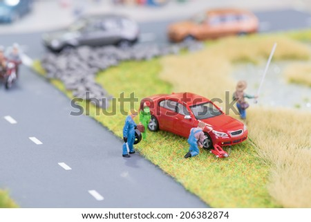 Miniature mechanic replacing a punctured tyre off the roadway - stock photo