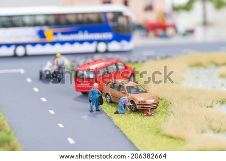 Miniature mechanic replacing a tyre at the roadside  - stock photo
