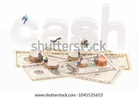 Miniature men and women sitting on coins and cash wooden letters